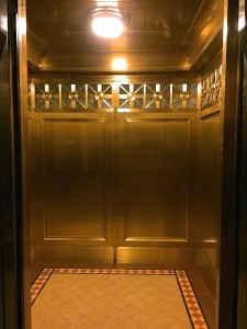 Elevator cab interior consists of custom bronze wall panels with fabricated grecian grills.
