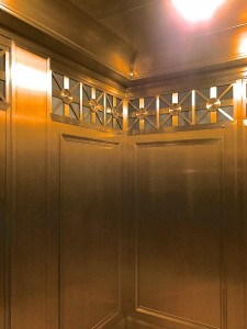 Elevator cab ceiling in bronze with a custom curved  crown moulding.