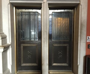 Fabricated bronze doors with oxidized finish. Cast bronze custom moldings & medallions. Fabricated grill work sandwiched between 2 layers of glass (no pinch hazard from either side).